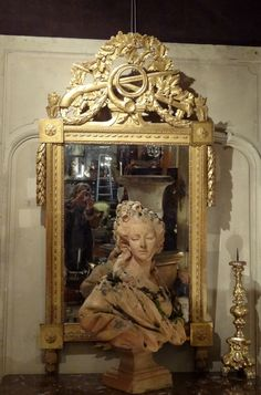 Mirror in carved and #gilt wood #LouisXVI. Pediment decorated with oak leaves and garlands, to the attributes of hunting. #Provence, #18th century. For sale on Proantic by Laurence Helmer et Maison James.