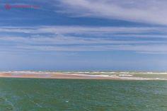 O delta do São Francisco, entre Alagoas e Sergipe, com uma duna de areia dividindo o mar do rio. O céu é azul e a água, verde.