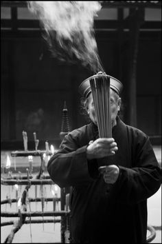 CHINA. Sichuan Province. Chengdu. The ZHAJUE Buddhist Temple. A devotee in traditional Chinese dress and hat offers incense sticks.