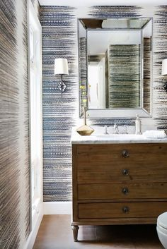 Bathroom with a large silver mirror, stripped wallpaper, and a wooden dresser