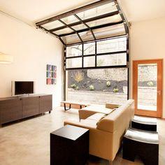 On aime le vitrage 'asymétrique' dans la porte coulissante verticale.  Le contraste des  cadrages noir, le blanc minimaliste des mur et la présence de bois se coordonne parfaitement