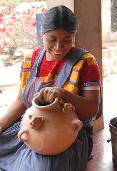 a Maya woman laughs as she paints a jaguar olla. Amatenango del Valle Chiapas Mexico