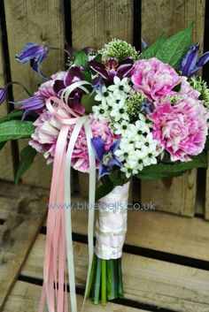 Bridesmaids bouquet in carnations, chincherinchee, clematis, orchids and trachelium with trailing satin ribbons