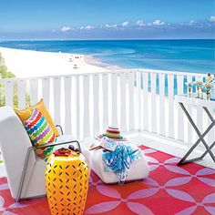 The bold reds, pinks, and oranges on this patio make the water seem even more blue.
