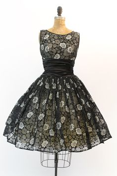 Gorgeous 1950s party dress! Done in a black velvet flocked organza. The white scattered daisies make the pattern pop! Wide gathered flattering satin