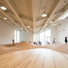 Children's play areas located beneath the zigzag roof of this community centre by Japanese architect Kengo Kuma have been landscaped to form a hilly indoor terrain that can be clambered over or used as slide.