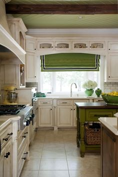A few green accents -- window treatments, painted island and fruit bowl and vases in this kitchen that was designed by Tobi Fairley. (WOW Factor: Check out the ceiling!!)