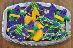 Mardi gras decorated sugar cookies. Royal icing. Yellow, gold, purple, green. Mask, fleur de lis, music note, harlequin.