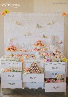 Lace backdrop, hanging pearls, teacups. Put a wooden board over top open drawers to create extra shelves