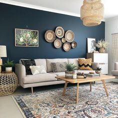 A Dark Blue Accent Wall With Cream Sofa Wicker Baskets Used As Art And