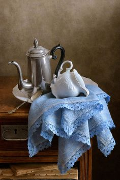 Kitchen still life with metal vintage teapot, white milk jug and blue folded napkin on wooden table lighted by daylight