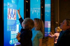 """A family visiting the New England Aquarium interacts with a three-screen multitouch interactive exhibit. Ideum developed the custom exhibit software and designs and produces the Presenter 65"""" touch walls."""