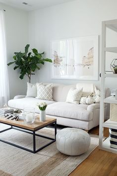 A beautiful Living room with a sofa and white colored cushions, some accessories on the table, a dark white colored rug,A beautiful wall canvas print into this white colored room. It's a beautiful Modern and classic living room decoration. http://www.urbanroad.com.au/