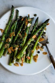 NYT Cooking: Cooking asparagus is one of the easiest kitchen tasks around. There is almost no preparation, the asparagus is roasted plain in the oven, and all that's left to do is fry some almonds and capers to spoon on top. This can be served as part of a festive spread of salads and seasonal dips. It also works well as a side for meat, fish or grain dishes.