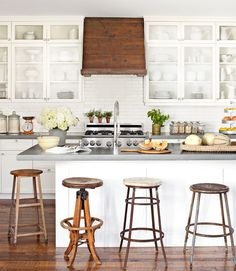 An assortment of old stools provides quirky charm in the kitchen of this Oregon home. The durable concrete countertops are from Cement Elegance.   - CountryLiving.com