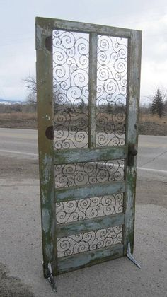 Spirals of Barbed Wire In Upcycled Door..Would make a beautiful garden gate or room divider.
