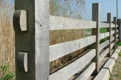Oak post and rail fence with hidden rail joints and oak peg fixings.  Design : Kevin Barton