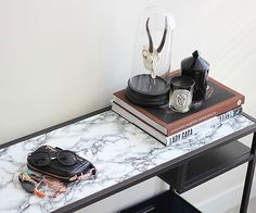 If cutting straight lines isn't your forte, you'll appreciate this faux marble table tutorial from Syl and Sam. As the DIY bloggers explain, your edges don't have to be perfect when you're covering a removable table top that sits flush in its frame. Of course, it also helps when your marble contact paper has handy grid lines on its backing. /