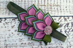 Esta diadema de flores de fieltro en niveles se hace a mano con cuatro filas de hojas de delicioso y suave lana fieltro verde musgo, aqua, ciruelo y rosa violeta. La flor mide aproximadamente 5 x 3.5 y es acentuado con un arco de 3 de musgo verde con una cola de arco de doble capa de musgo y aqua.  El arco es acentuado con un centro rosa de diamantes de imitación brillantes. Las Dalias de fieltro, arco y diamantes de imitación son mano cosida a un suave 5/8 ejército verde Satén cinta elá...