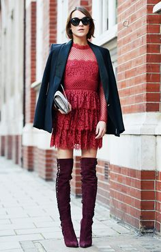A red lace mini dress is worn with a black blazer, thigh-high suede boots, and black sunglasses
