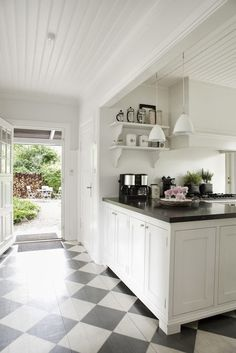 Black and white painted floors in a white country modern kitchen