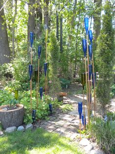 Blue bottles and copper pipe instead of an arbor for the entrance to a garden