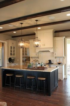 Rustic Kitchen with Planked Hardwood Floors, White Cabinetry, Painted Island, Wood Beams and Beautiful Lighting.