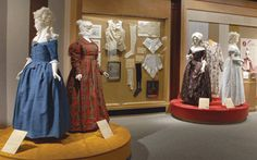 1780s blue wool worsted gown from Connecticut, and a plaid wool pelisse (ladies' robe) of about 1725 from Massachusetts. A display case includes dated silk stockings (1781) and 18th-century items from Massachusetts Governor Belcher (1682-1757) and his wife. Gowns and a painted man's banyan from the late 18th or early 19th century represent style in cotton.