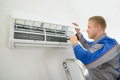 Technician repairing air conditioner. http://photodune.net/item/technician-repairing-air-conditioner/10202886