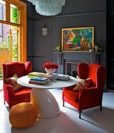 fauteuils de couleur carmin, lustre baroque, mur gris, peinture murale