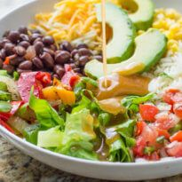 A photo of a white bowl with romain lettuce, shredded cheddar cheese, cilanto lime rice, tomato salsa and black beans being topped with delicious Chipotle Honey Vinaigrette (Copycat).