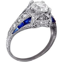 """""""The Rhiannon"""". A row of brilliant cut diamonds flanking a 1.12ct Old European cut center diamond. Accented with 12 fancy-cut dark blue sapphires, set in hand-engraved milgrained platinum."""