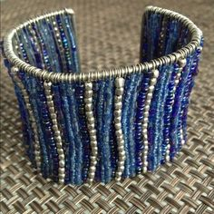blue & silver beaded cuff Such a cool, sassy cuff bracelet! Blue & silver beads sparkle and shimmer off of your wrist. This beauty can be worn casually w/ denim or dressed up w/ your LBD. Unique piece! Excellent condition! boutique Jewelry