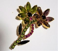Mid Century multi color rhinestone flower brooch Fuchsia pink, purple, olive green and black prong set rhinestones Gold tone setting 2 x 3 inches Unsigned Gorgeous matching earrings are available Very good vintage condition, shows no wear International buyers welcome, shipping is automatically combined, over charges are refunded Priority shipping is offered 71917  Credit cards and Paypal accepted  Please visit my other pins: https://www.etsy.com/your/shops/GretelsTrea...