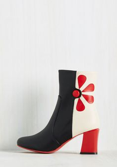 Just when you thought your eclectic footwear rotation was at the top of its curation, these go-go boots make themselves known - and they must join your caboodle! Irresistibly retro with red petals, buttons, and glossy, angular heels, these black and white stunners from Banned perfectly complete your collection.