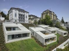 At once bold and contextual, this series of slope-side urban dwellings manages to look modern and yet related to the historic civic buildings located on the street above.