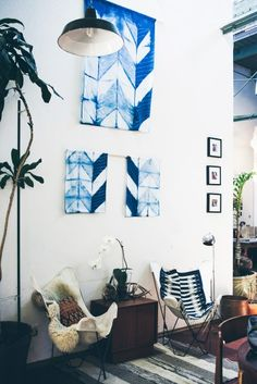 textile wall art + butterfly chairs + white walls + striped rug