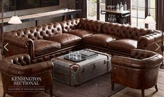 Restoration Hardware Kensington Sectional vintage leather brown tanned ultimate chesterfield sofa.  The interior design here features an industrial aluminum trunk coffee table, industrial bar cart and vintage shuffle board that both have reclaimed wood, a series of antique patent drawings on the wall, and industrial-styled floor lamps
