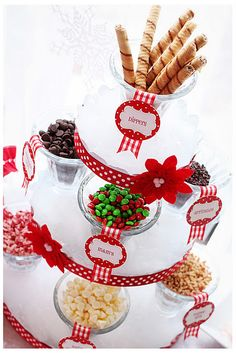 "Food labels from the Candy Christmas printables set were used to label sundae glasses filled with various store bought yummies like M&M's, chocolate chips and toffee. Batting was used under the glasses to simulate ""snow"" and some ""softness"" to the metal stand."