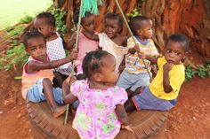 Beautiful Ugandan orphans swinging on the tire swing at the Baby Home.