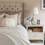 bedrooms: pale mauve walls gray linen tufted headboard gray duvet pink mauve pillows metallic pink pillow white shag pillow white wool rug white nightstand silver lamp