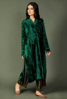 A phiran in stunning deep green chenille fabric, enhanced with zari embroidery in Mughal patterns. This phiran, handcrafted in luxurious chenille, features tiny zari embroidered flowers on the sleeves and stitch lines at the neck. Velvet Pakistani Dress, Pakistani Bridal Wear, Pakistani Dress Design, Frock Fashion, Batik Fashion, Women's Fashion Dresses, Pakistani Fashion Casual, Pakistani Dresses Casual, Indian Fashion