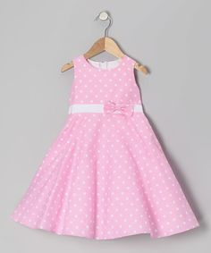 Peppered with polka dots and embellished with a prim bow, this soft frock fits fabulously thanks to a half zipper and cinching sash in back.