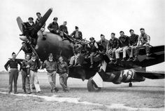 """Pilots of the 63rd Fighter Squadron, 56th Fighter Group posing for a """"team photo"""" on one of their P-47s in England during WWII"""