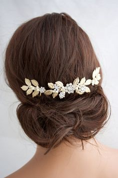 Balancing out the right amount of accessories with your wedding day look doesn't have to be nearly as complicated as it seems. For an updo, simply find a clip or comb that mirrors the lines of your style. For example, this bold clip echoes the pattern of this low chignon, creating an instant statement.