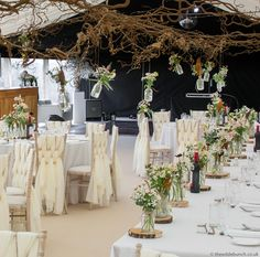 A late Summer / Autumn marquee design by top Bristol Florists, The Wilde Bunch. An overhead matrix of contorted hazel with hanging designs over the tables. Marquee Wedding, Florists, Late Summer, Bristol, Canopy, Garland, Wedding Flowers, Tables, Autumn