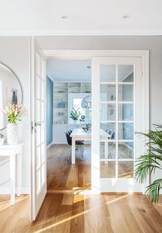 Beautiful bright dining room with Scandinavian decor - light blue walls, customised bookcase, french doors and a stunning silver lamp from Tom Dixon, all fits perfectly to the warm wooden floor.