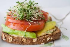 whole grain toast, hummus, avocado, tomatoes, and sprouts