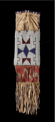 """Lakota Beaded """"Flag"""" Tobacco Bag. ДА2.3 small American flags across the top of the 10"""" x 7 1/2"""" beaded panel; remainder of the panel features geometric designs in red, blue, yellow and brass beads. The reverse has crosses, triangles and mountains in green, blue and gold on a white field. Quill wrapped drop holding fringe is 13 1/2"""" long making the bag 28 1/2"""" overall. Circa 1890s. Brian Lebel's High Noon Auction, Jan. 2015."""