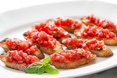 Bruschetta with tomato and basil! Chopped fresh tomatoes with garlic, basil, olive oil, and vinegar, served on toasted slices of French or Italian bread. #healthy #vegan On SimplyRecipes.com